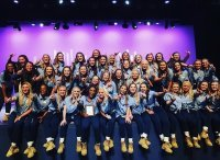 Large group of Zeta Tau Alpha members in denim shirts, jeans, and work boots pose on stage after performing in the University's step sing competition.