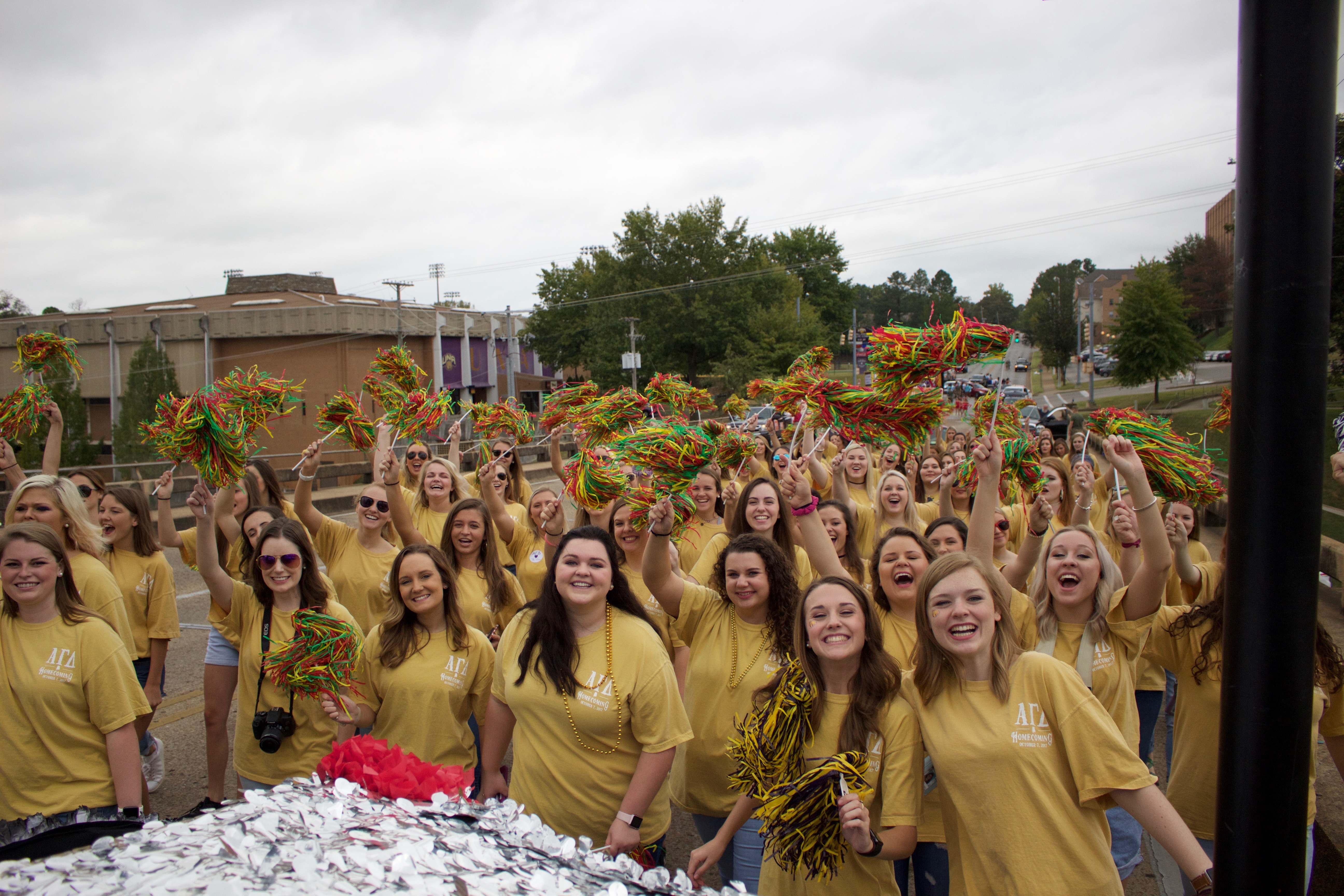 Women in yellow shirts cheering with green, red, and yellow poms during homecoming parade