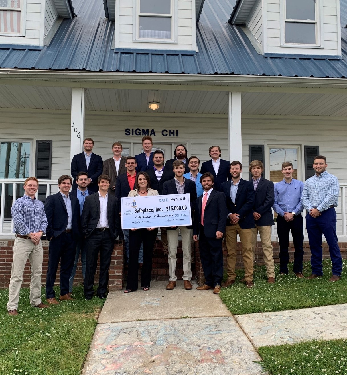 The brothers of sigma chi stand outside their house with a representative from Safe Place, presneting the charity with a $15,000 check from the fraternity's derby days competition.