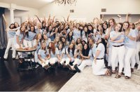 About 30 members of Phi Mu members pose in matching light blue shirts before a recruitment event.
