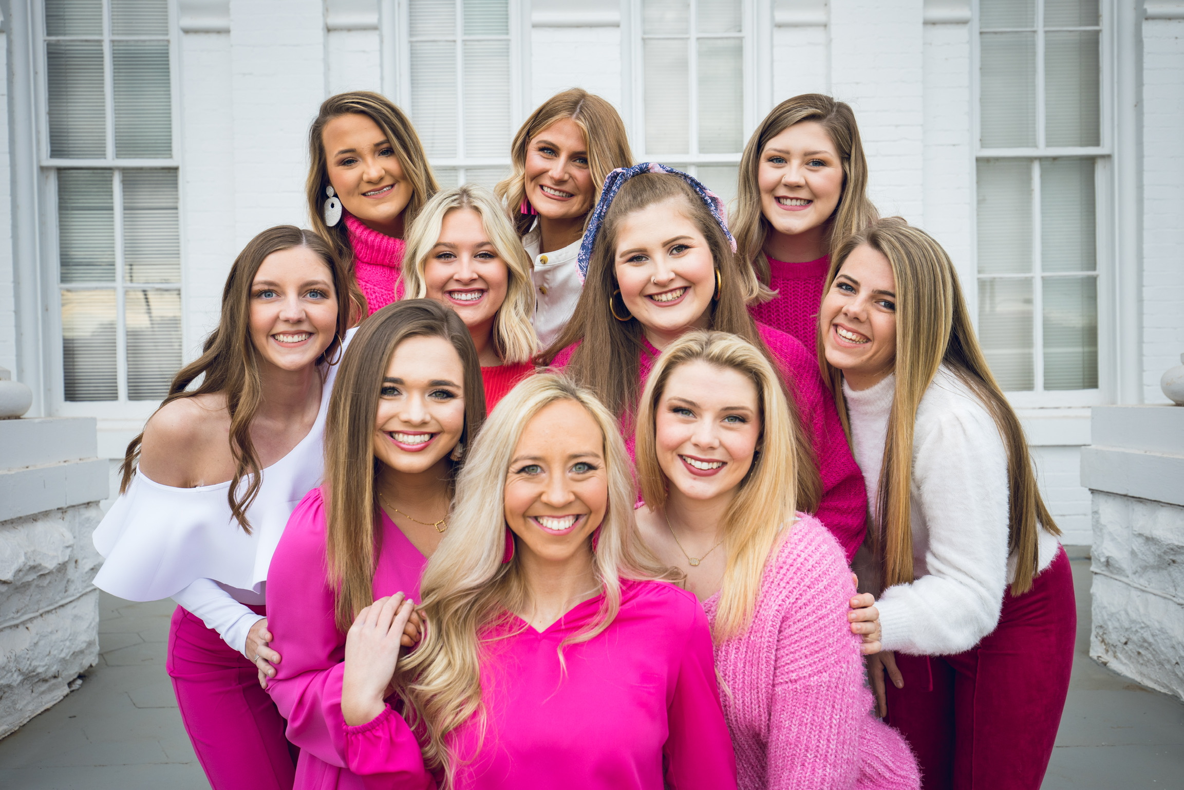 10 women in pink outfits gather and smile for a photo.