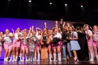Members of Phi Mu gather on stage in costume with the step sing trophy after winning in spring 2020.