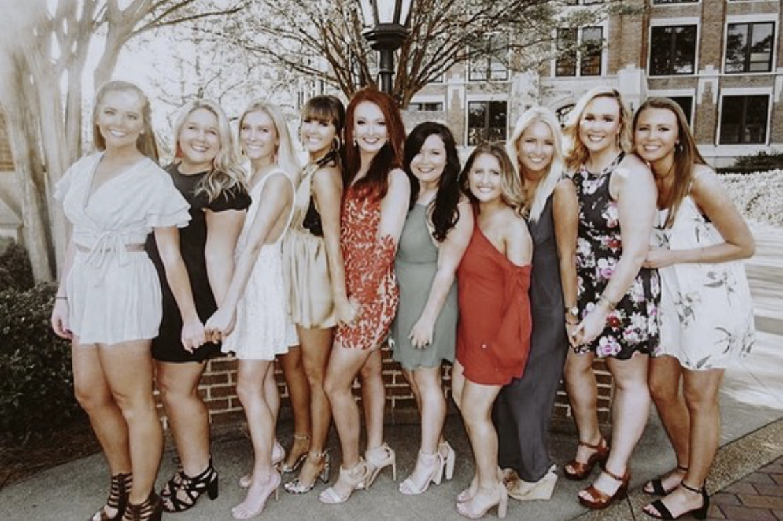Alpha Gamma Delta members in dresses, holding hands, smiling.