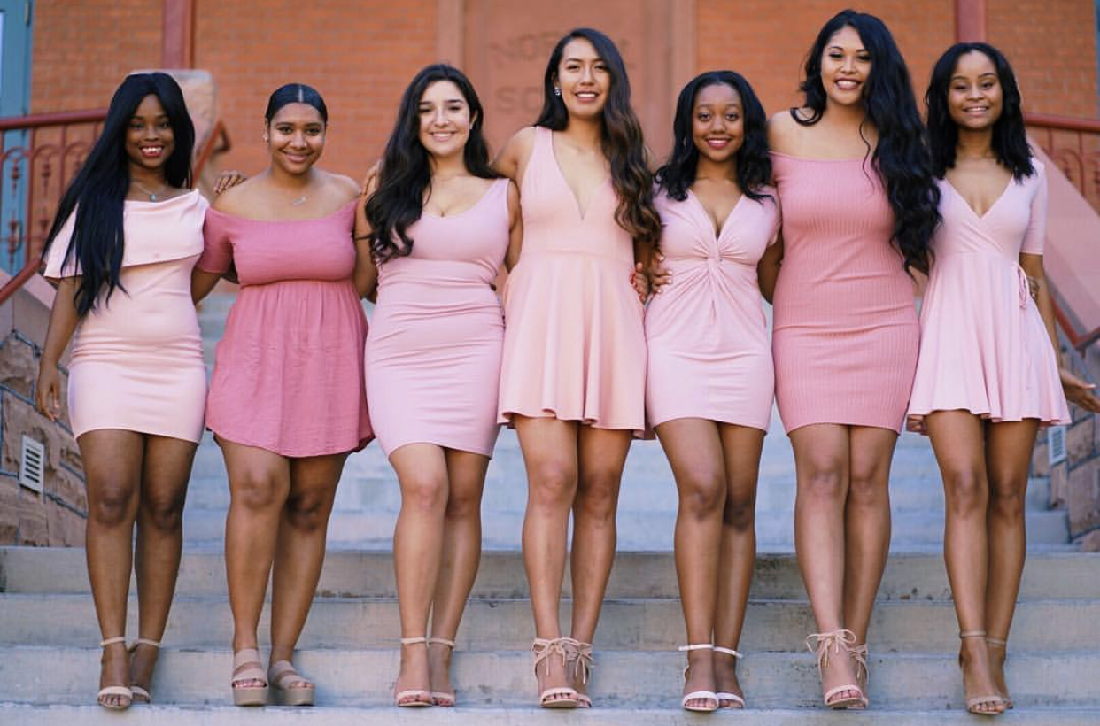 A group of diverse women in pink dresses gathered together, smiling.