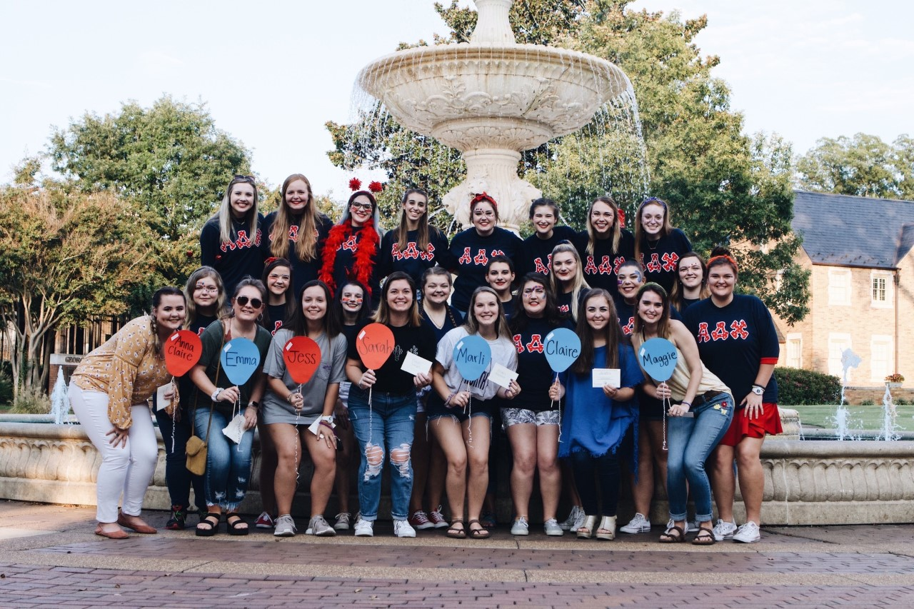 Members of Alpha Delta Chi pose for a group photo in front of the fountain