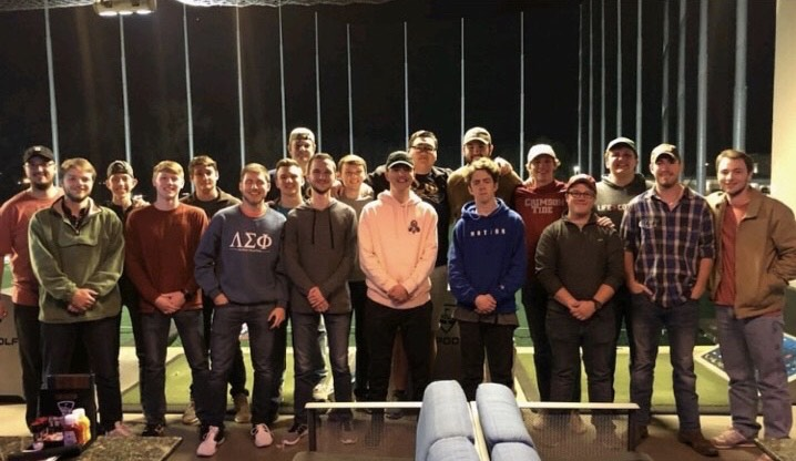 Members of Lambda Sigma Phi pose for a photo together at Top Golf