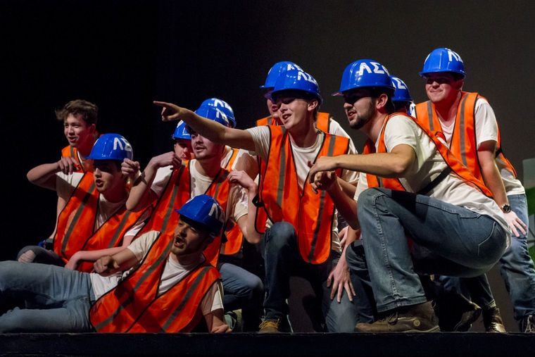 Men in orange vests and blue hats gathered on stage during step sing performance, themed