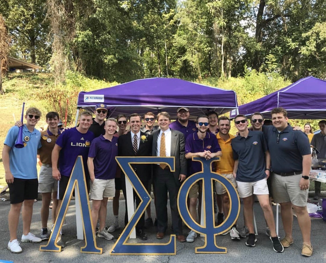 Members of Lambda Sigma Phi gather under a pop-up tent at a tailgate and pose behind large wooden Lambda Sigma Phi letters